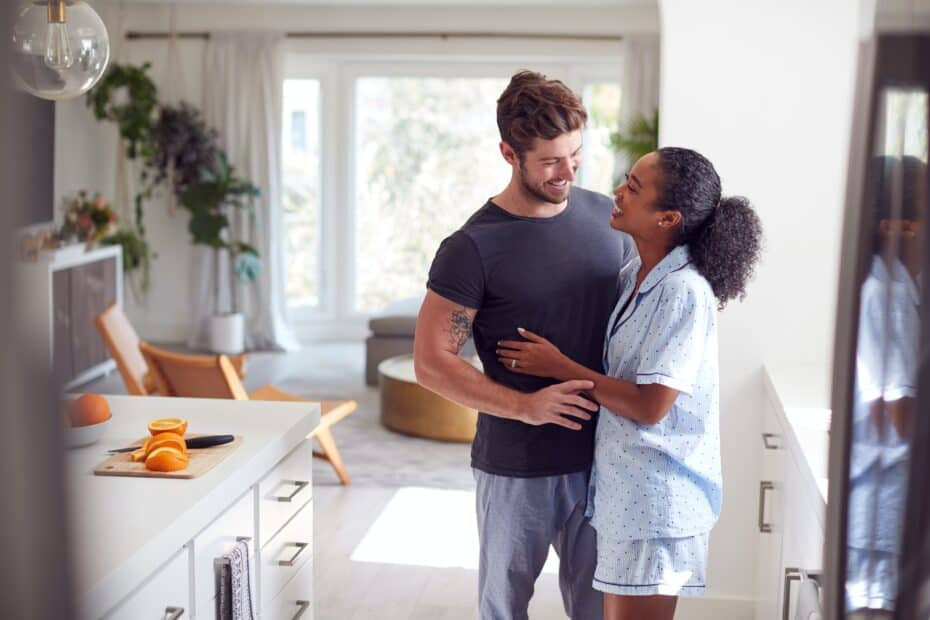 Loving Couple Wearing Pyjamas Hugging In Kitchen At Home Together