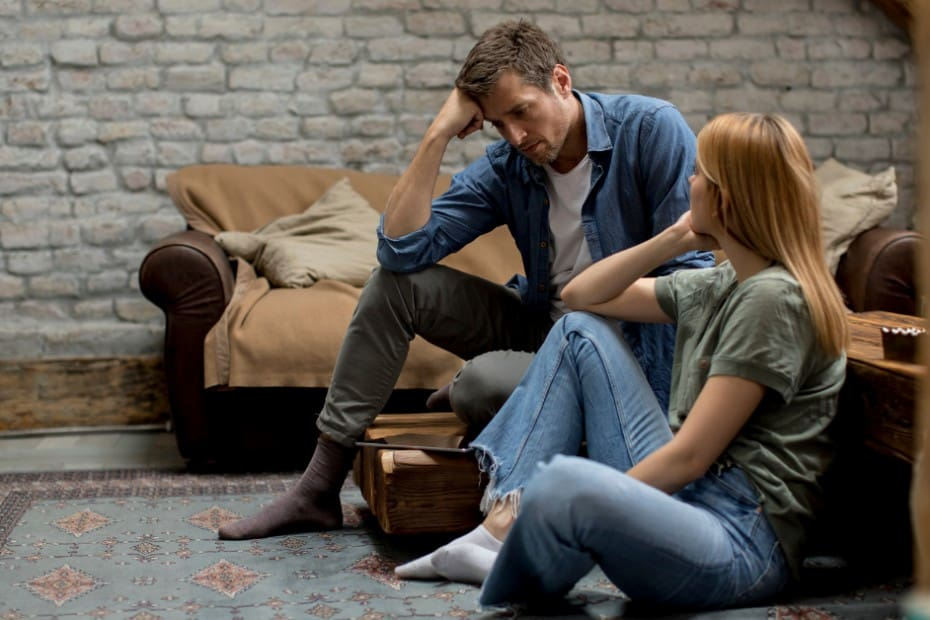 A heterosexual couple sitting in their living room on the floor. The man is resting his head on his right hand that is propped up on his right knee. The women is looking over her right shoulder towards the man. They look upset.