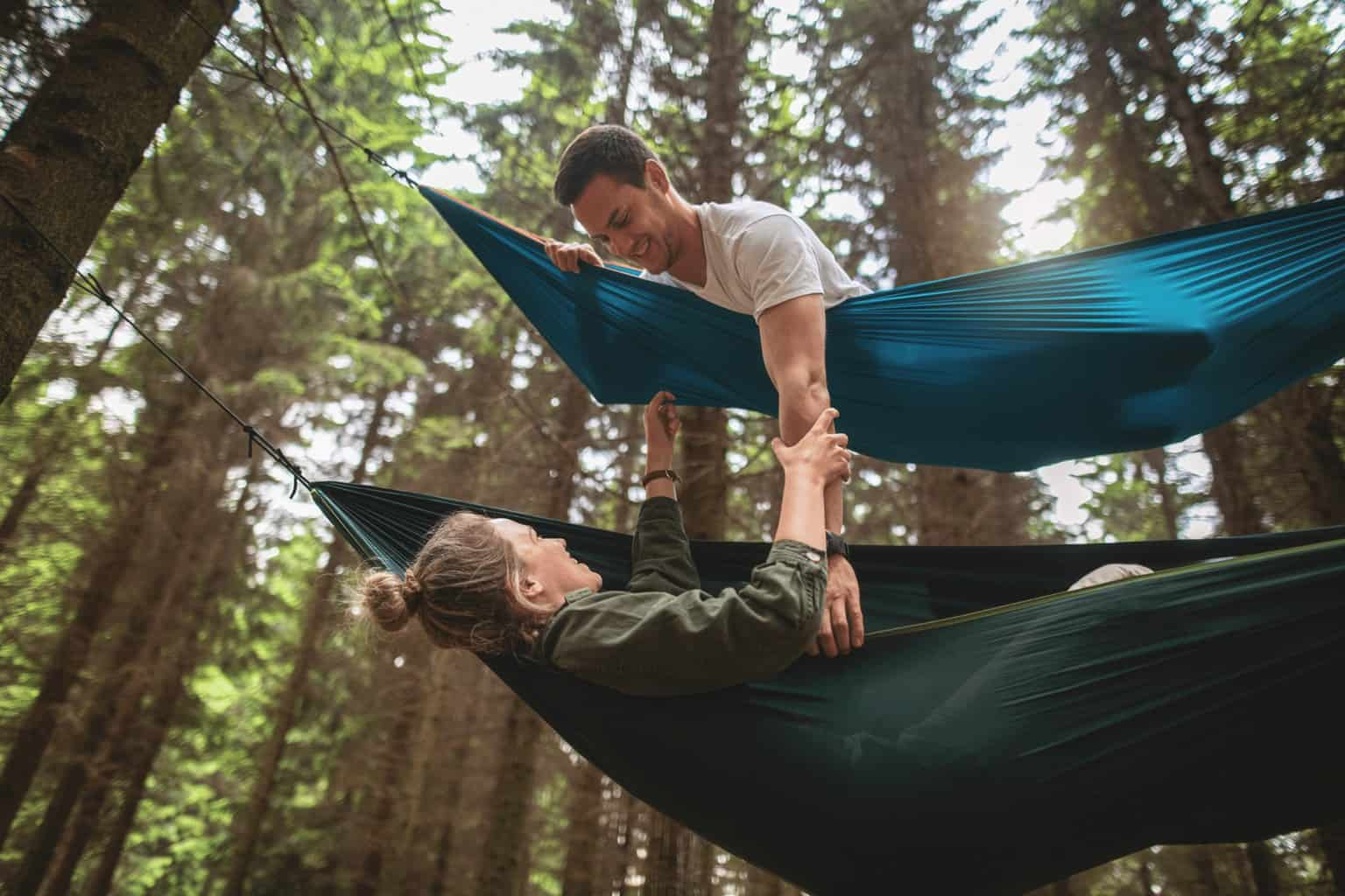 Playful couple laying in two seperate hammocks in the pine forrest. The camera is at a low angle, looking up. The woman is in a green hammock reaching up to the man in the blue hammock who is looking down at her. They both look very happy and lots of playfulness towards each other..