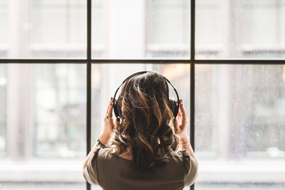 A person standing in front of a semi-opaque window wall. They have medium length curly brown hair and are facing the window. They are wearing a brown shirt, bracelets, and boho rings. They have over-the-ear headphones on and are pressing their hands into them.